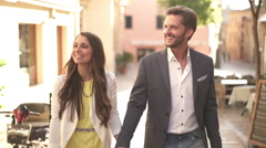 Well dressed young couple walking in pedestrian zone Stock Footage