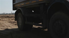 Tipper with large black wheels is driving past the camera. Stock Footage