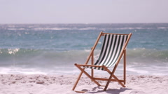 A deck chair is in the sand Stock Footage