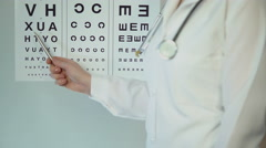 Female oculist pointing at table with small letters, checking patient's eyesight - stock footage