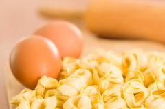 Closeup tortellinis piled up next to an egg and blurry rolling pin background - stock photo