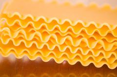 Lasagne plates with wave shaped pattern stacked upon each other - stock photo