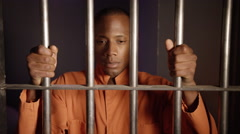 Modern Prison - African American Man Tilt up holding bars Stock Footage