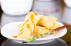 Springrolls elegantly placed on white plate with some soya sauce covering Stock Photos