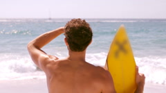 A man is looking at the sea with his surfboard Stock Footage