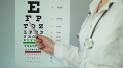 Eye doctor examining patient's eyesight, pointing at medical table with letters - stock footage
