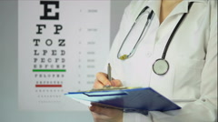Hard-working optician prescribing medication to patient at clinic, healthcare - stock footage