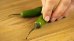 Slicing organic serrano pepper on wood cutting board. Stock Footage