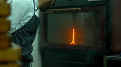 Restaurant chef looking on the fire in the oven. 120 FPS slow motion shot - stock footage