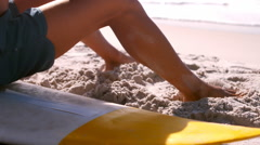 A man is sitting on his surfboard Stock Footage