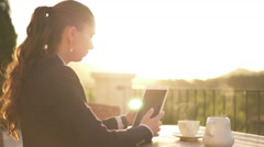 Young business woman with digital tablet and coffee on balcony Stock Footage