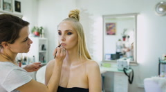 Finishing touch. In the salon for beautiful blondes do makeup. Makeup artist Stock Footage