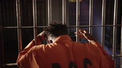 Corrections and Prison Culture - Man behind bars looking out - stock footage
