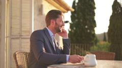 Business man talking on iphone outside on terrace Stock Footage