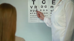 Eye doctor checking eyesight of female patient, reception at the ophthalmologist - stock footage
