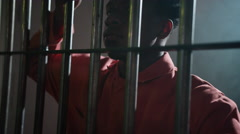 Prison cells in Jail - African American man in orange jump suit - stock footage