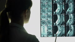 Female doctor looking at roentgen image, neck X-ray, diagnosing patient - stock footage