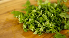 Slicing fresh organic cilantro on wood cutting board. Stock Footage