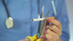 Doctor's hands cutting a cigarette with scissors, anti-tobacco campaign, habit Stock Footage