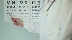 Female oculist pointing at table with small letters, checking patient's eyesight Stock Footage