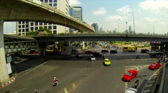 Bangkok's traffic with BTS sky trains passing by. Silom intersection. Stock Footage