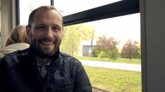 Portrait of happy, young man during tram ride in city, super slow motion 240fps Stock Footage