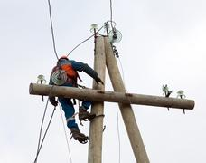 Electrician working on the power lines after the accident Stock Photos