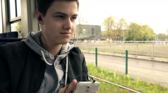 Young teenager listen to music on cellphone during tram ride, super slow motion  Stock Footage