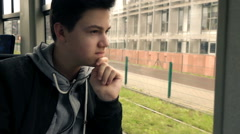 Pensive teenager looking out of window while riding tram, super slow motion 240f Stock Footage