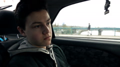 Pensive, young teenager sitting in car, super slow motion 240fps Stock Footage