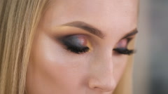 Burn look. Expressive makeup on the eyes, very pretty girl languidly looks in - stock footage