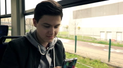 Young teenager using smartphone during tram ride, super slow motion 240fps Stock Footage