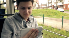 Young teenager watching movie on smartphone during tram ride, super slow motion  Stock Footage