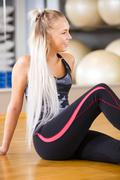 Smiling fitness woman sitting in workout outfit at the gym - stock photo
