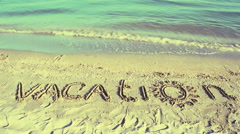 The inscription Vacation on sand. Stock Footage