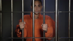 Young woman behind bars in jail cell - stock footage