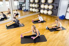 Group stretching exercises for muscle flexibility at fitness center Stock Photos