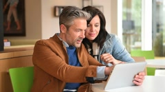 Mature couple in coffee shop connected on internet - stock footage