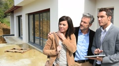 Couple with realtor visiting house under construction Stock Footage