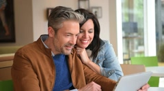 Mature couple in coffee shop connected on internet Stock Footage