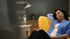 Woman at home reading book in armchair - stock footage