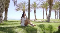 Single woman sitting among palm trees Stock Footage