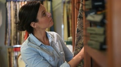 Woman in upholstery shop looking at fabric samples Stock Footage