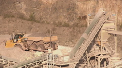 Dump truck unloads stone into a hopper for grading at Haughmond Quarry - stock footage