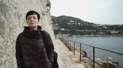 Woman tourist with backpack walking at the seaside along fortress with stone Stock Footage