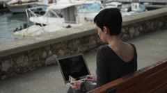 Woman pay online by credit card on the laptop at the landing stage Stock Footage