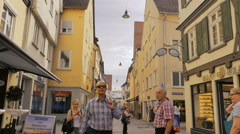 Multiple people on phones busy narrow street Ulm Germany Stock Footage