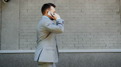 Caucasian businessman walk and calls by phone outdoors Stock Footage
