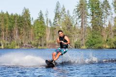 Young man riding wakeboard on summer lake - stock photo