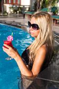 Young pretty blonde woman swimming pool with water melon cocktail Stock Photos